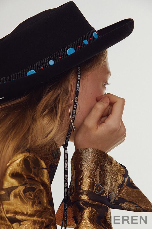 자카드 장식 메탈릭 골드 컬러 코트 루이 비통 LOUIS VUITTON, 스톤 장식의 펠트 소재 해트 디올 DIOR, 왼쪽 귀에 착용한 골드 도금 스털링 실버 소재 클립온 이어링, 오른쪽 귀에 착용한 뿔 디자인 이어링 샬롯 슈네이 BY 분더숍 CHARLOTTE CHESNAIS BY BOONTHESHOP.